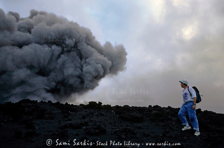 Tourist walking near the smoke billowing from the crater of Yasur Volcano, Tanna Island, Vanuatu.